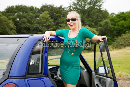 young woman smiling by electric car