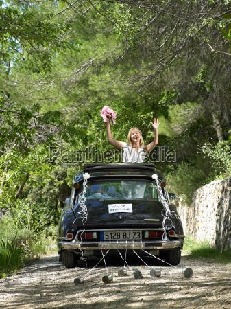 bride waving from wedding car