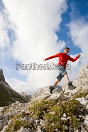 man jumping from rock to rock