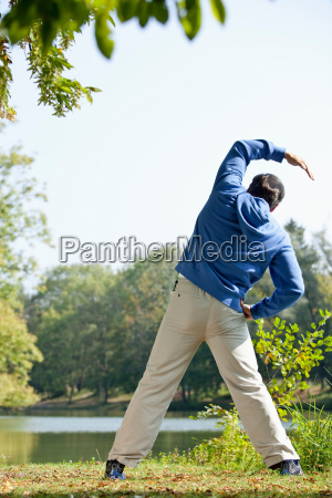 man stretching beside lake