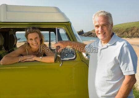mature couple with vintage camper van