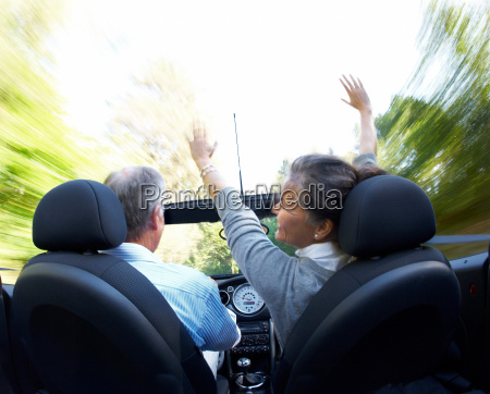 mature couple driving sports car