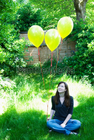 happy woman with balloons in garden