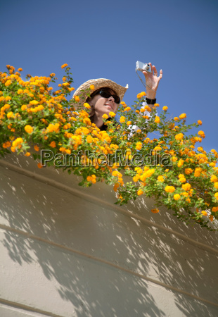 woman taking photograph by flowers