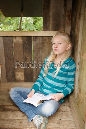 young girl reading in treehouse