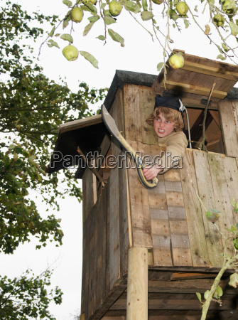 boy playing in treehouse