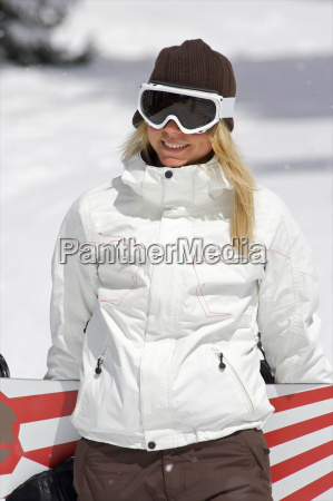 female snowboarder walking with her snow