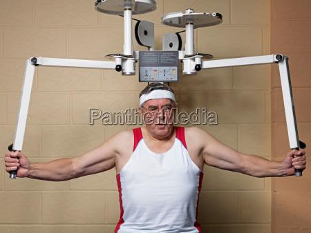 senior male exercising at gym