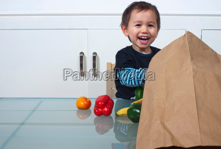 child with bag of groceries