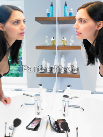 frau die sich selbst im spiegel