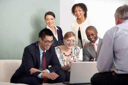 a business group around a laptop