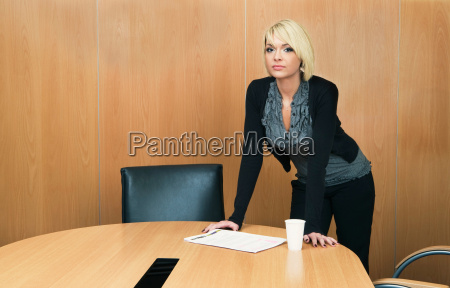 woman leaning on boardroom table