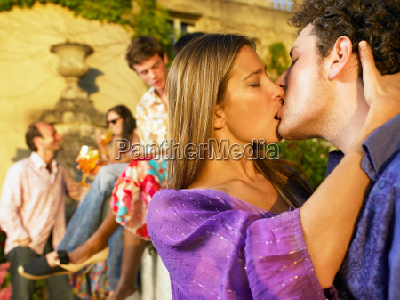 couple kissing at a cocktail party