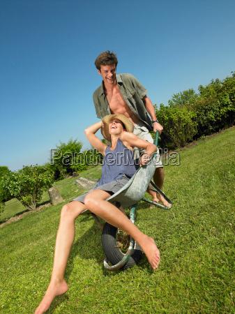 man pushing woman in a wheelbarrow