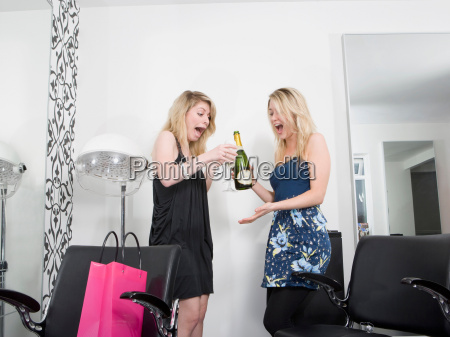 two women at hairdressers with champagne