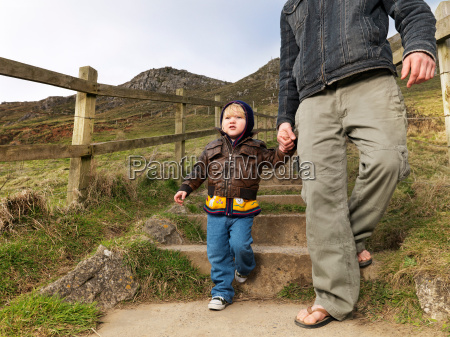 child walking with father on hill