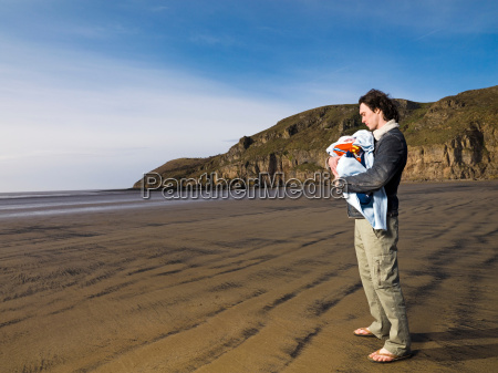 man on beach holding baby