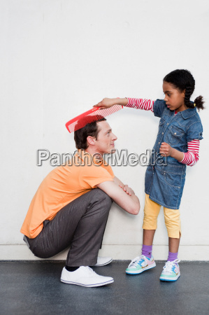 man being combed by young girl