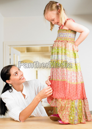 woman adjusting a girls dress