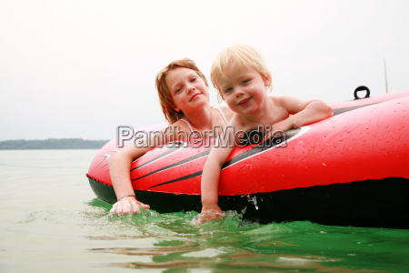 girl and boy swimming with rubber