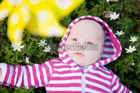 baby lying in grass beneath toy