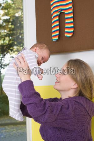young woman uplifting her baby
