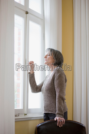 old woman standing at window