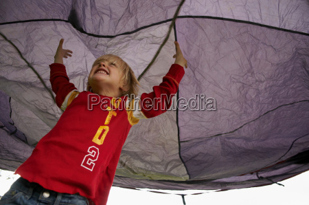 boy playing under tent