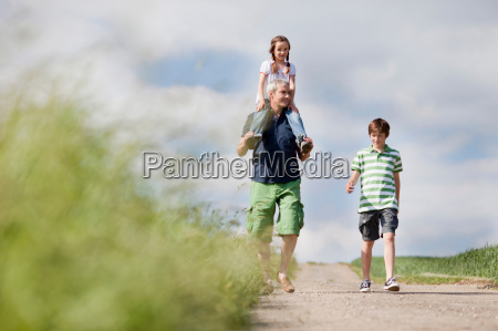 family of three walking down the
