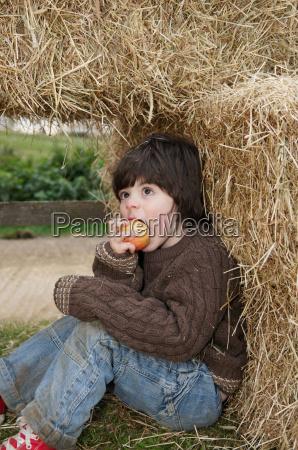 young boy in hay bales