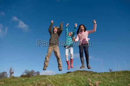 three children jumping on hill