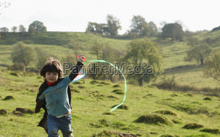 young boy running with kite in
