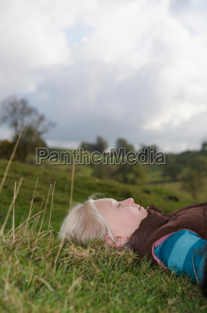 girl lying on grass looking at