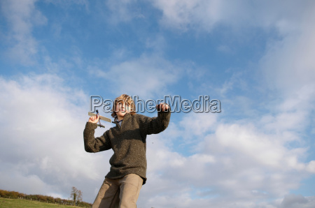 boy with toy plane in countryside
