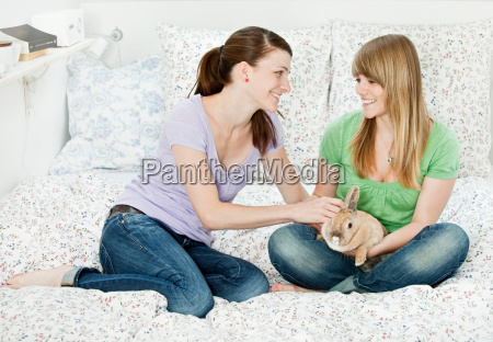 two young woman with pet rabbit