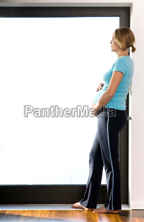 pregnant woman looking out a window