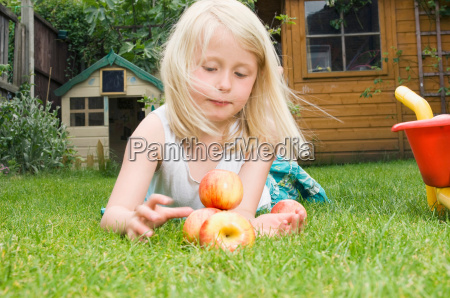 young girl playing with apples