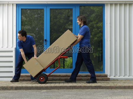 two men carrying boxes on trolley