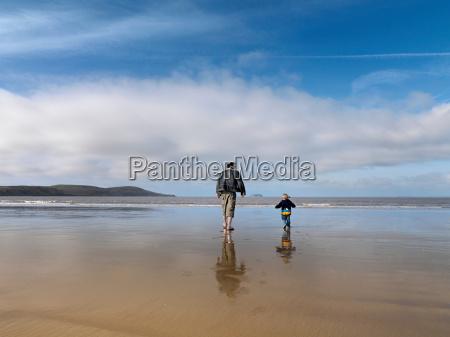man and child walking towards sea
