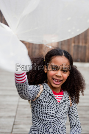 young girl playing with toy wings