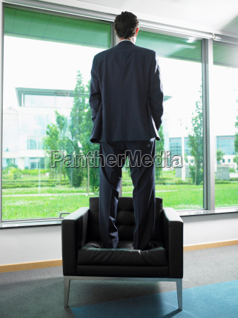 man standing on a armchair
