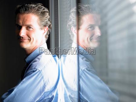 man against window smiling