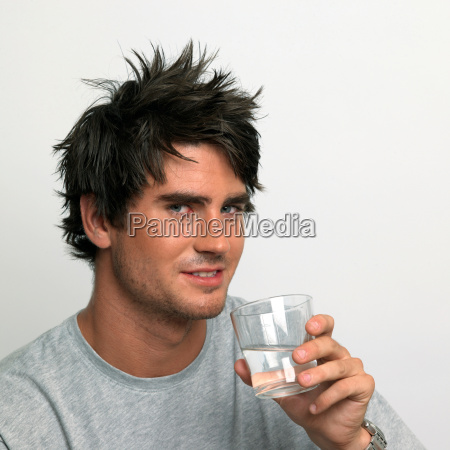 young man drinking a glass of