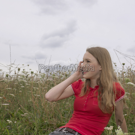 young woman in grass with mobile