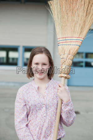 young girl with broom smiling
