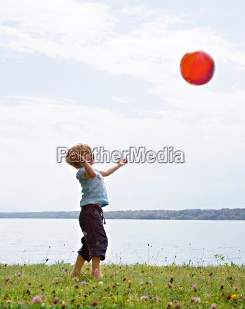 boy playing with ball at lake