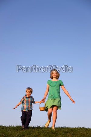boy and girl running holding basket