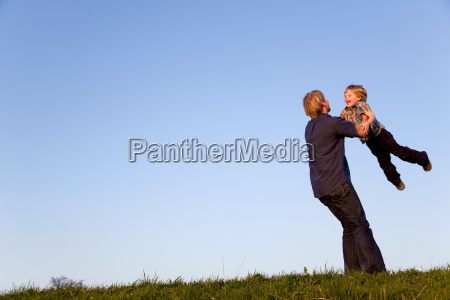 father spinning boy in his arms