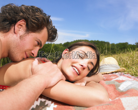 couple on blanket in field