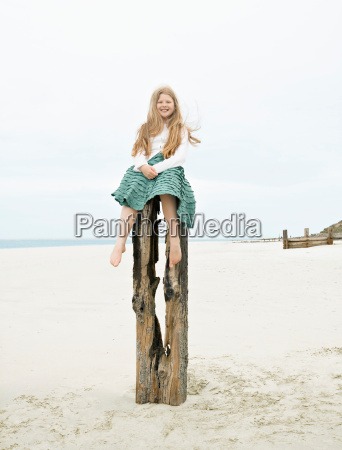 girl sitting on top of post